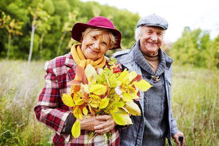 parejas felices: Feliz femenino de nivel superior con hojas de oto�o mirando a la c�mara en el parque