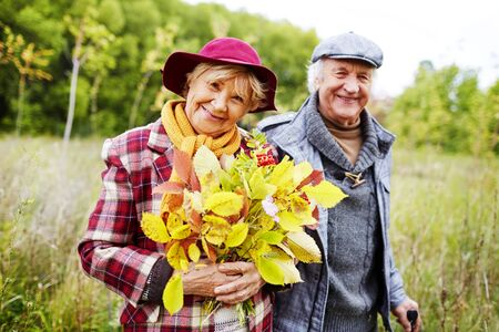 uomo felice: femminile maggiore felice con le foglie d'autunno guardando la fotocamera nel parco