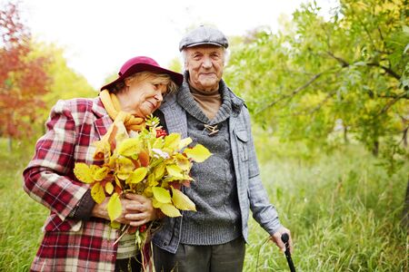 old man happy: Happy senior woman with autumn leaves leaning to her husband in park Stock Photo