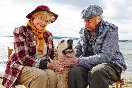 señora mayor: Pareja de jubilados jugando con su mascota al aire libre