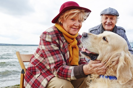 Retired woman cuddling cute pet with her husband on background