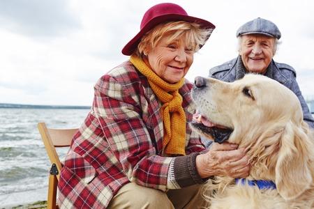 marido y mujer: Mujer jubilada abrazos linda mascota con su marido en el fondo Foto de archivo