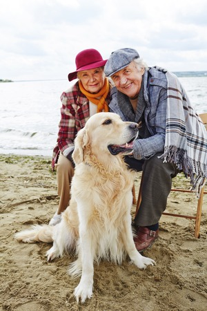 Retired couple with labrador spending time by seaside Stock Photo - 45115671