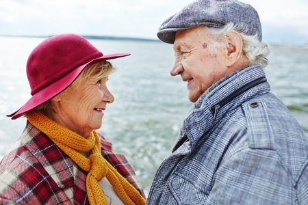 Retired couple in warm clothes looking at one another by seaside