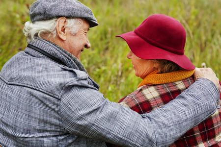 personas abrazadas: Volver la vista de las personas mayores cariñosos que interactúan en el medio natural