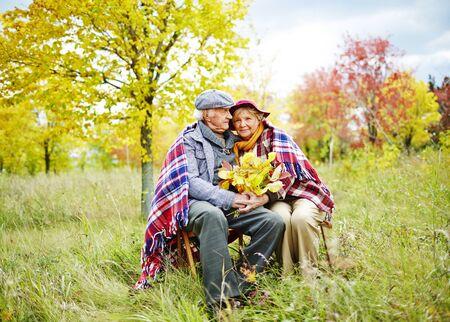 ancianos felices: Viejo hombre y mujer en ropa de abrigo que se sienta en el parque en el ocio