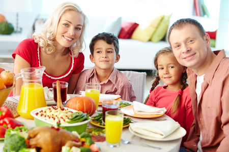 thanksgiving dinner: Happy young family sitting at celebration table on Thanksgiving Day and looking at camera