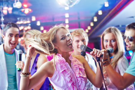 karaoke: Pretty girl singing at party on background of happy friends Stock Photo