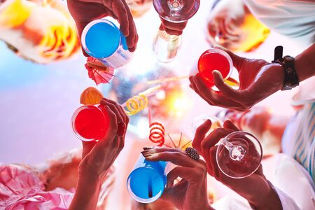 Cocktails held by friends at party photo
