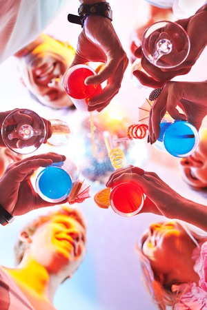 Cocktails in friends hands during toast photo