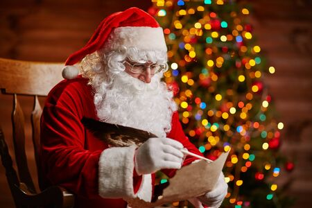 letter writing: Santa Claus answering Christmas letter by sparkling firtree