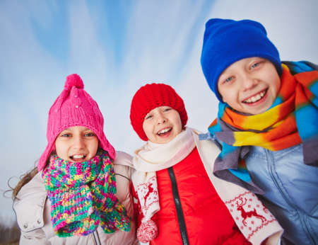 winterwear: Joyful kids in winterwear looking at camera with smiles