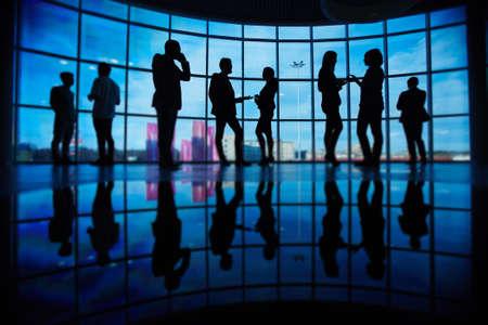 personas comunicandose: Contornos de la gente de negocios la comunicación en la reunión contra la ventana