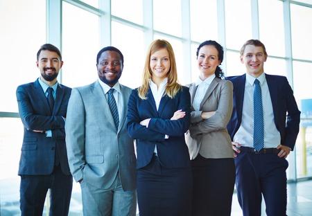 Groep van succesvolle mensen uit het bedrijfsleven in formalwear kijken naar de camera