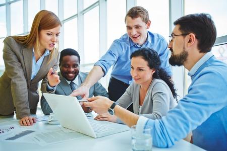 Groep medewerkers te kijken naar de gegevens in de laptop en uiten hun ideeën tijdens de vergadering Stockfoto