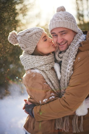 amorous woman: Amorous young woman kissing her happy boyfriend on winter day Stock Photo