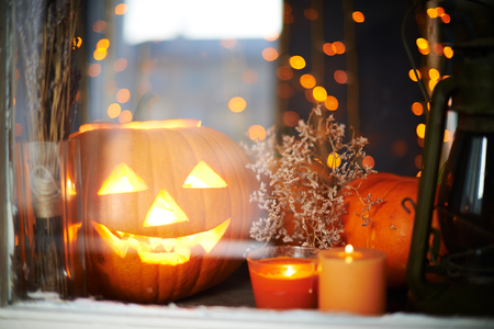 antichrist: Halloween pumpkin and burning candles in window