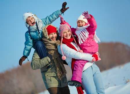 man portrait: Ecstatic family looking at camera in winter