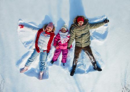 Happy family of three having fun in snowdrift