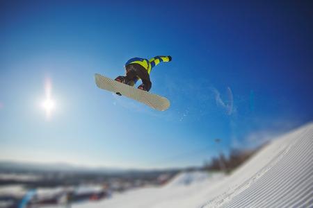 snowboarding: Sportsman snowboarding in winter against blue sky