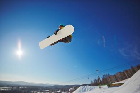 sportsman: Sportsman on snowboard hanging over snowdrift Stock Photo