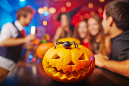 friends at bar: Carved pumpkin and spider on background of group of friends celebrating Halloween in bar Stock Photo