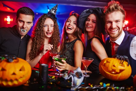 Halloween witches and vampires having cocktail party in bar