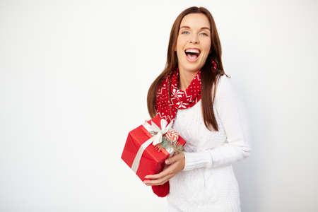 ecstatic: Ecstatic girl with Christmas gift looking at camera Stock Photo