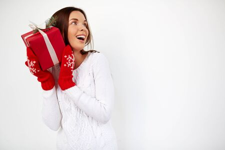 guess: Surprised girl with Christmas gift by her ear Stock Photo