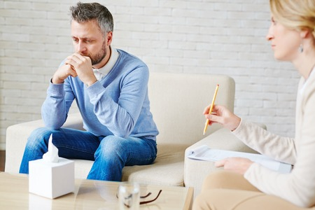 man and women: Sad man sitting by his psychologist Stock Photo