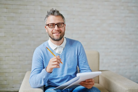 Male psychiatrist with pencil and clipboard looking at camera Stockfoto