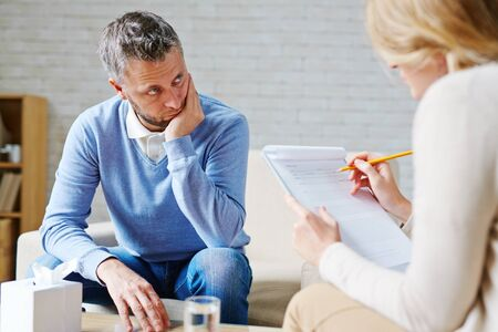 tense: Tense man looking at his psychologist during consultation