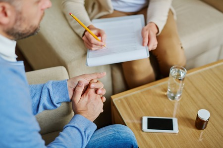 counsel: Male sitting in armchair while psychiatrist making notes in medical document Stock Photo