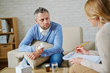 despaired: Despaired man with pillow and handkerchief looking at his psychologist during consultation