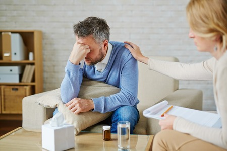 despaired: Despaired man with pillow and handkerchief being reassured by his psychologist