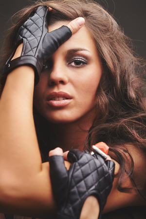 glam rock: Pretty glam rock girl in black leather gloves looking at camera