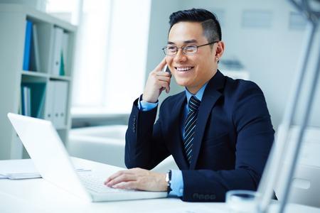 gente exitosa: Joven empresario asiático en las lentes que llama en oficina