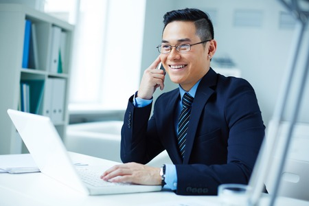 asian business: Young Asian businessman in eyeglasses calling in office