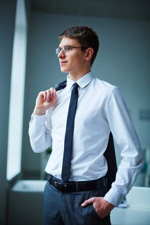 standing businessman: Young elegant businessman standing by window in office Stock Photo