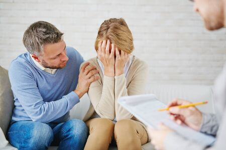 despaired: Anxious man reassuring his wife while visiting psychologist