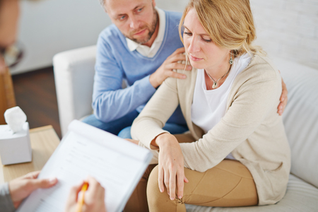 adult crying: Unhappy woman and her anxious husband visiting psychologist together