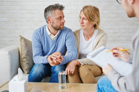psychologist: Sad couple sitting on sofa in front of psychologist Stock Photo