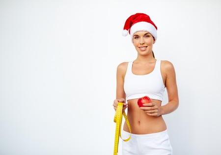 activewear: Fit young woman in Santa cap and activewear holding red apple and measuring tape