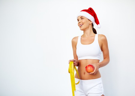 activewear: Ecstatic girl in Santa cap and activewear holding red apple and measuring tape Stock Photo