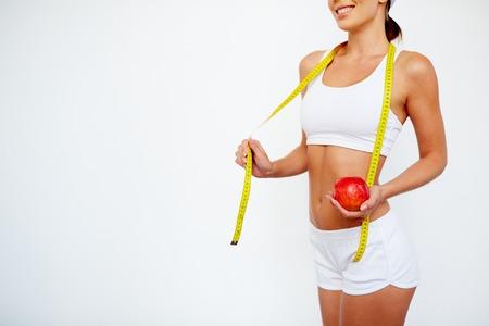 cinta metrica: Muchacha delgada con la manzana y la medición de pie de cinta en forma aislada