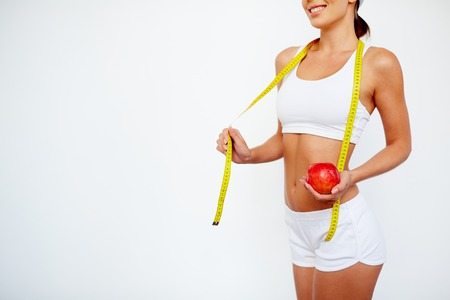 slender: Slender girl with apple and measuring tape standing in isolation