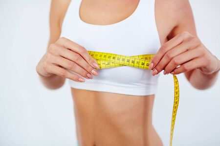 activewear: Young female measuring size of chest