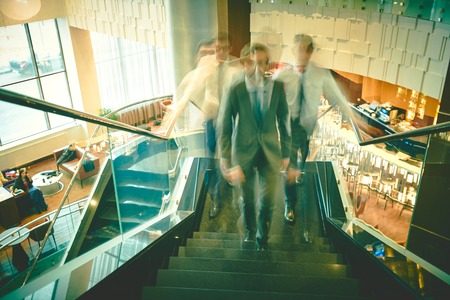upstairs: Blurred outlines of businessmen going upstairs