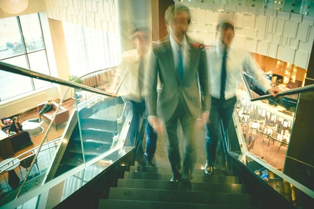 upstairs: Blurred outlines of business group going upstairs