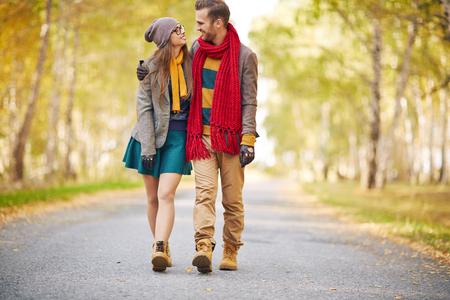 parejas caminando: Pareja joven con estilo que recorre en el parque en otoño
